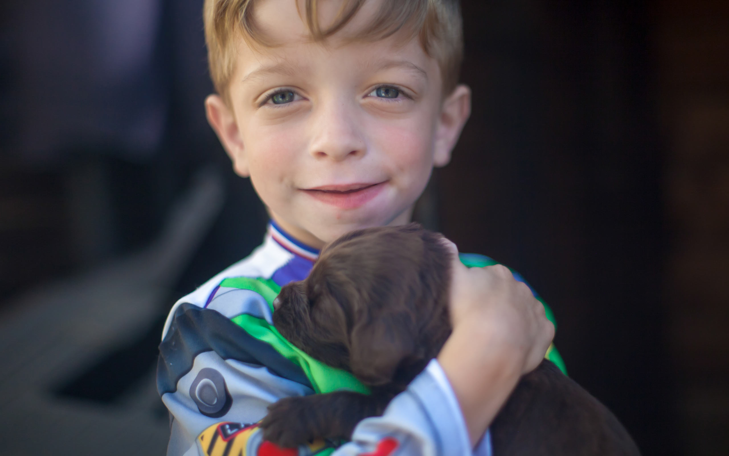 Albie, diagnosed with LAL-D as an infant, holding a puppy